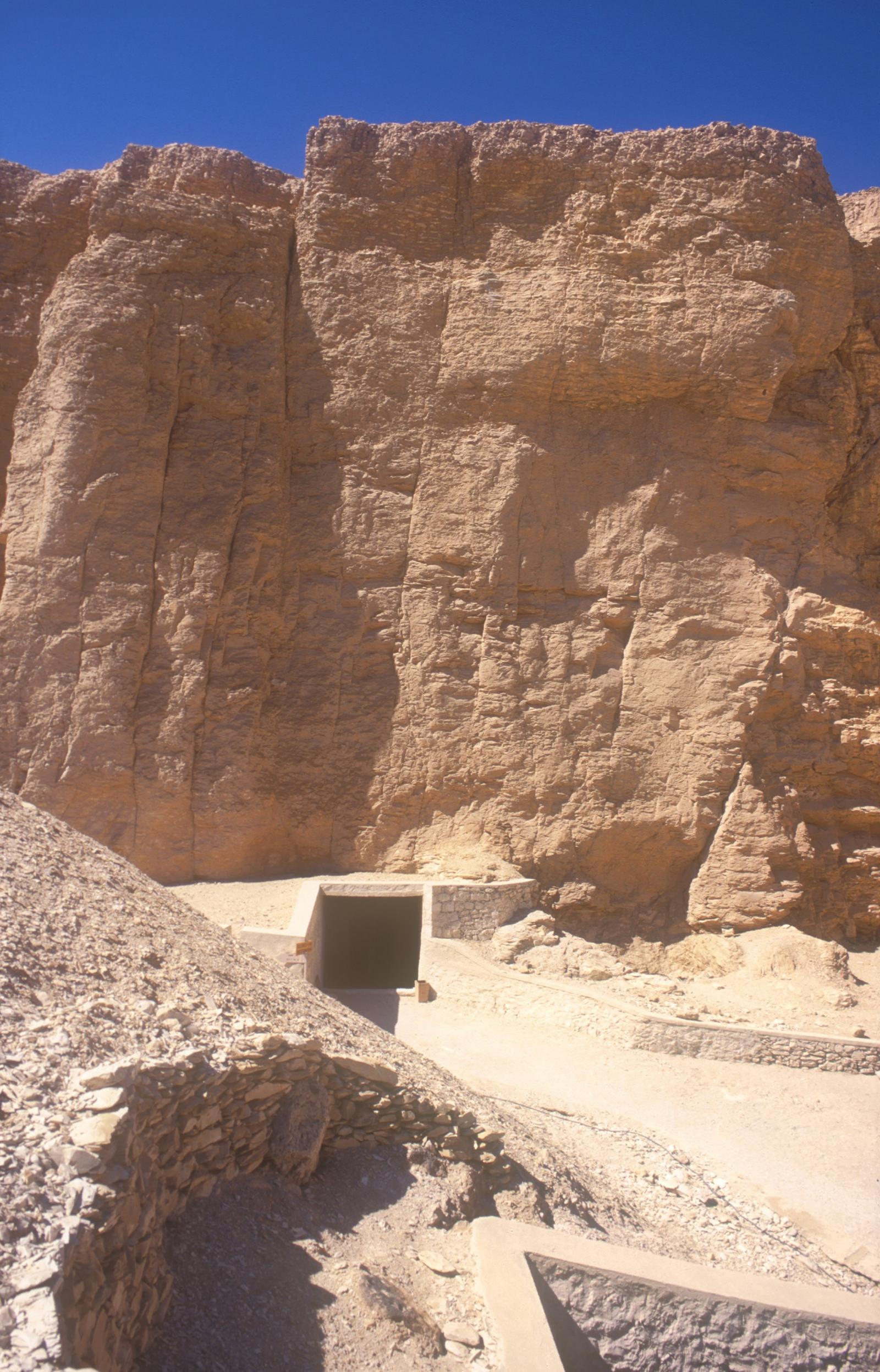 Tomb entrance at base of cliffs with modern covering for flood protection.