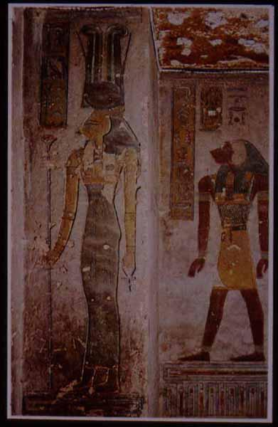 "Hathor, ""mistress of the west,"" in the tomb of Rameses III, in a relatively rare represenation with the head of a cow and two tall ostrich feathers, along with the cow horns and sun disk more usual to this goddess.  In the background is the monkey-headed"