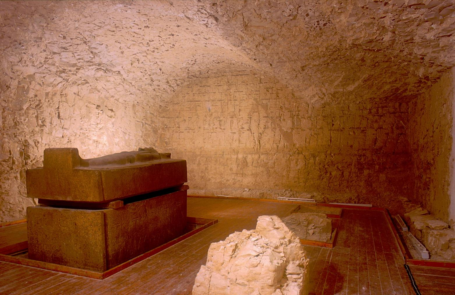 Sarcophagus in undecorated burial chamber with modern flooring.