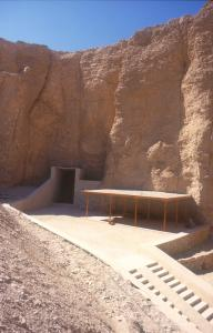 General view of the tomb entrance at base of cliff with modern covering, adjacent shelter, and modern approach path.