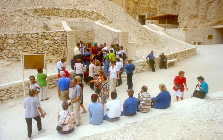 Tourists at a tomb entrance.